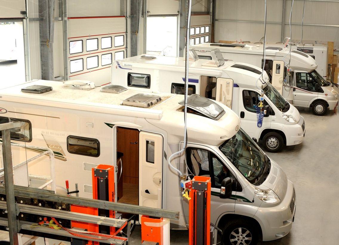 Überblick in Werkstatt mit drei Wohnmobilen