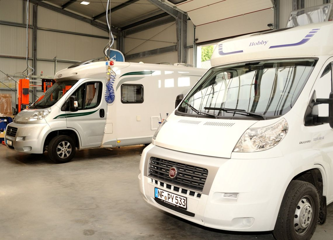 Zwei Wohnmobile in Werkstatthalle