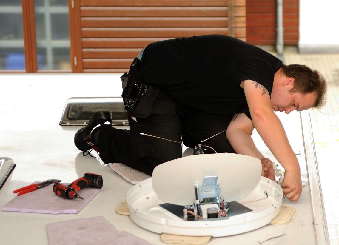 Mann schraubt an Solaranlage