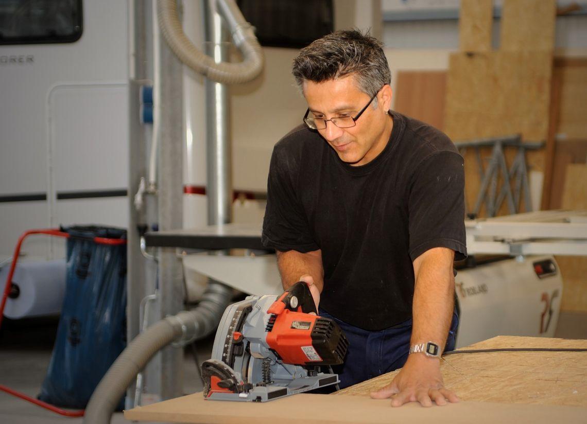 Mann sägt ein Stück Holz zurecht